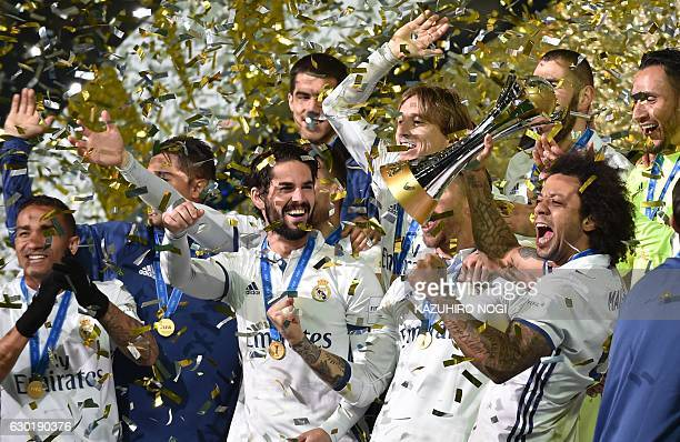 Real Madrid defender Marcelo and his teammates celebrate with their trophy after winning the Club World Cup football final match between Kashima...