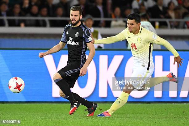 Real Madrid defender Nacho Fernandez fights for the ball with Club America forward Silvio Romero during the Club World Cup semifinal football match...