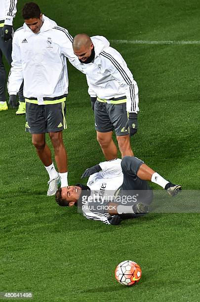 Real Madrid defenders Raphael Varane and Pepe share a smile as Cristiano Ronaldo gestures on the ground after falling during a training session ahead...
