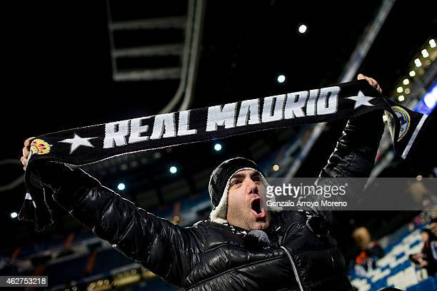 Real madrid fan poses for a picture with a Real Madrid scarf before the La Liga match between Real Madrid CF and Sevilla FC at Estadio Santiago...