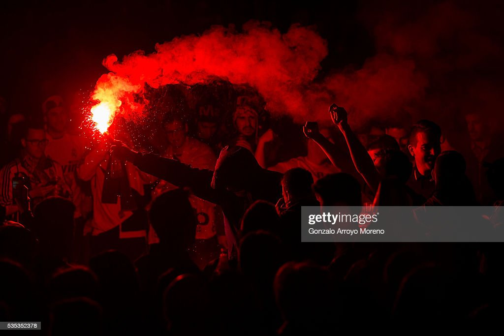 Real Madrid fans light a flare as they wait for their team at Cibeles Square after winning yesterday's Uefa Champions League Final against Club Atletico de Madrid on May 29, 2016 in Madrid, Spain.