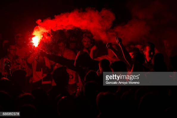 Real Madrid fans light a flare as they wait for their team at Cibeles Square after winning yesterday's Uefa Champions League Final against Club...