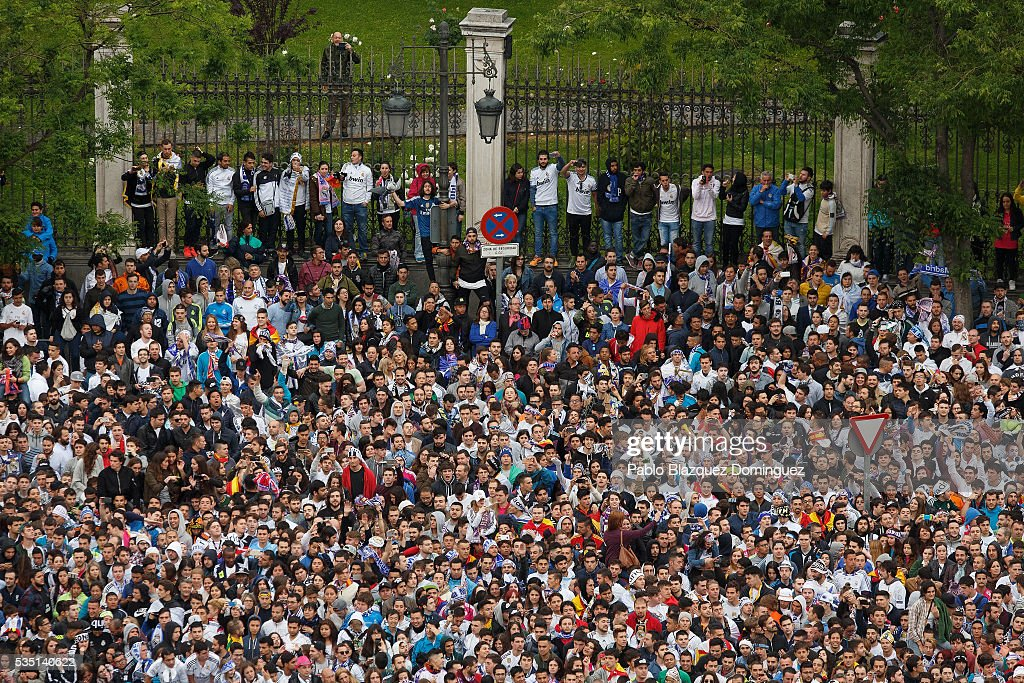 Real Madrid fans stand as they watch at their team celebrating at Cibeles Square after winning the Uefa Champions League Final match against Club Atletico de Madrid on May 29, 2016 in Madrid, Spain.