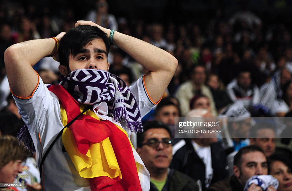 A Real Madrid football club supporter gestures after a goal by Atletico as he watches on a big screen at the Santiago Bernabeu stadium in Madrid on May 28, 2016 the UEFA Champions League final foobtall match between Real Madrid CF, Club Atletico de Madrid held in Milan, Italy. / AFP / CURTO