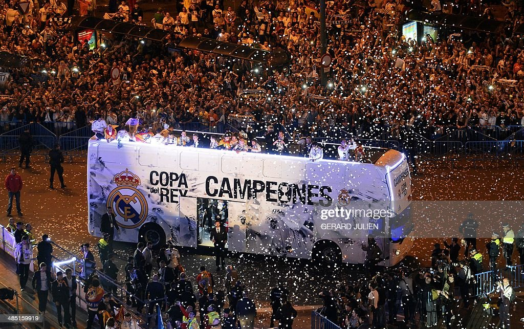 Real Madrid football squad's bus parades at Plaza Cibeles in Madrid as they celebrate their victory over Barcelona in the Spanish Copa del Rey (King's Cup) final 'Clasico' football match FC Barcelona vs Real Madrid CF early on April 17, 2014. Thousands of cheering Real Madrid fans welcomed their team back to the Spanish capital early on April 17, 2014 after they won the Copa del Rey with a 2-1 win over arch rivals Barcelona.