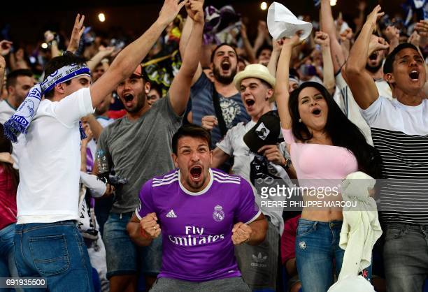 TOPSHOT Real Madrid football team fans celebrate their team's second goal on the stands of the Santiago Bernabeu stadium in Madrid on June 3 2017...