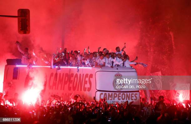 TOPSHOT Real Madrid football team fans surround the bus as Real Madrid players celebrate the team's win on Plaza Cibeles in Madrid on May 22 2017...