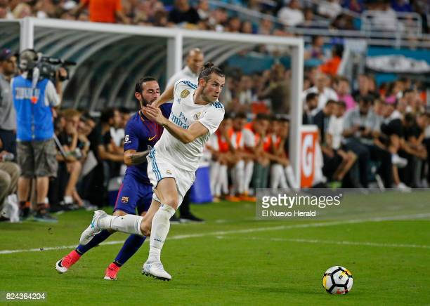 Real Madrid forward Gareth Bale right vies with Barcelona midfielder Arda Turan during the second half of ''El Clasico Miami'' as part of the...