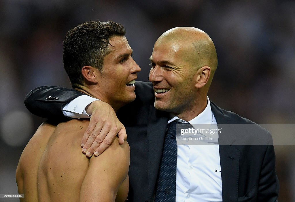 Real Madrid head coach <a gi-track='captionPersonalityLinkClicked' href=/galleries/search?phrase=Zinedine+Zidane&family=editorial&specificpeople=172012 ng-click='$event.stopPropagation()'>Zinedine Zidane</a> hugs a smiling <a gi-track='captionPersonalityLinkClicked' href=/galleries/search?phrase=Cristiano+Ronaldo+-+Soccer+Player&family=editorial&specificpeople=162689 ng-click='$event.stopPropagation()'>Cristiano Ronaldo</a> of Real Madrid after the UEFA Champions League Final match between Real Madrid and Club Atletico de Madrid at Stadio Giuseppe Meazza on May 28, 2016 in Milan, Italy.