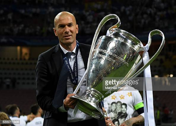 Real Madrid head coach Zinedine Zidane shows the trophy after winning the UEFA Champions League Final match between Real Madrid and Club Atletico de...