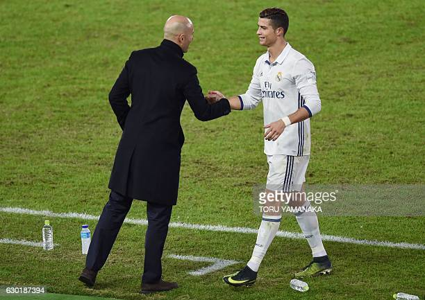 Real Madrid head coach Zinedine Zidane talks to player Cristiano Ronaldo as he is substituted during extratime of the Club World Cup football final...