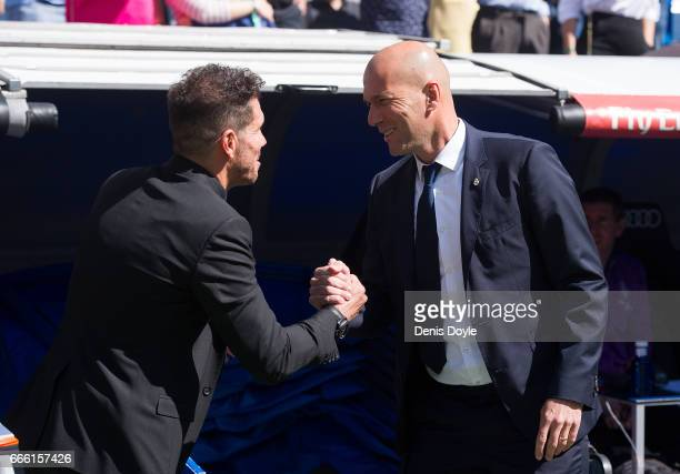Real Madrid manager Zinedine Zidane greets Head coach Diego Simeone of Club Atletico de Madri before the La Liga match between Real Madrid CF and...