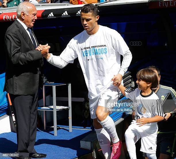Real Madrid mascot Zied a Syrian refugee holds the hand of Cristiano Ronaldo of Real Madrid as they walk out onto the pitch during the La Liga match...