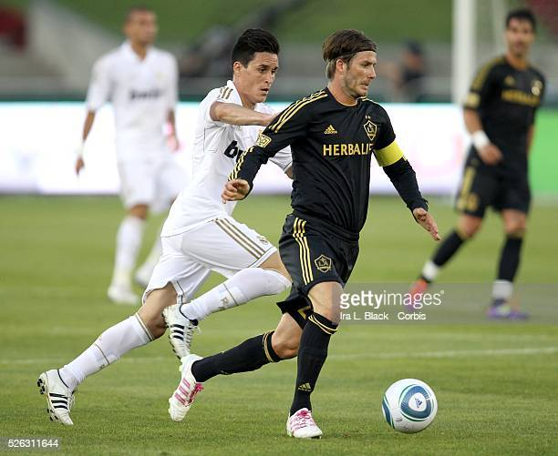 Real Madrid player Callejon tries to stop the advance by David Beckham during the Herbalife World Football Challenge Friendly match between LA Galaxy...