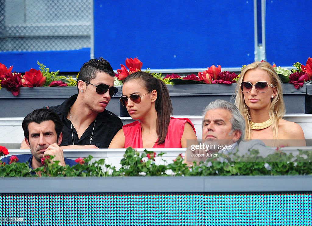Real Madrid player Cristiano Ronaldo (2nd L) chats with his girlfriend Irina Shayk while seated with Portuguese football legend Luis Figo (L) while attending the semi final match between Roger Federer of Switzerland and Janko Tipsarevic of Serbia during the Mutua Madrilena Madrid Open tennis tournament at the Caja Magica on May 12, 2012 in Madrid, Spain.