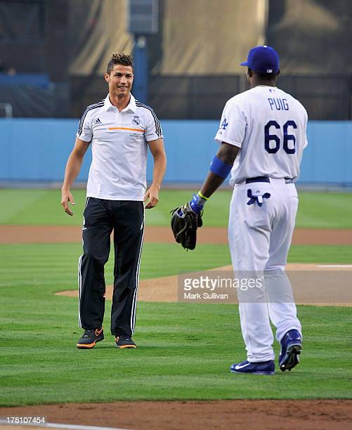 Real Madrid player Cristiano Ronaldo greets Los Angeles Dodger outfielder Yasiel Puig after throwing out ceremonial first pitch before the game...