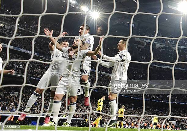 Real Madrid players celebrate Real Madrid's French forward Karim Benzema's goal during the UEFA Champions League football match Real Madrid CF vs...