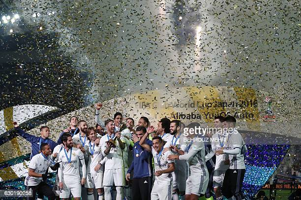 TOPSHOT Real Madrid players celebrate with their trophy after winning the Club World Cup football final match against Kashima Antlers of Japan at...