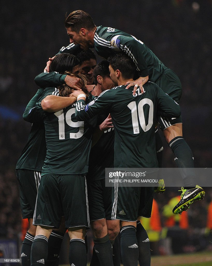 Real Madrid players crowd around Real Madrid's Croatian midfielder Luka Modric as they celebrate his equalising goal during the UEFA Champions League round of 16 second leg football match between Manchester United and Real Madrid at Old Trafford in Manchester, northwest England on March 5, 2013.