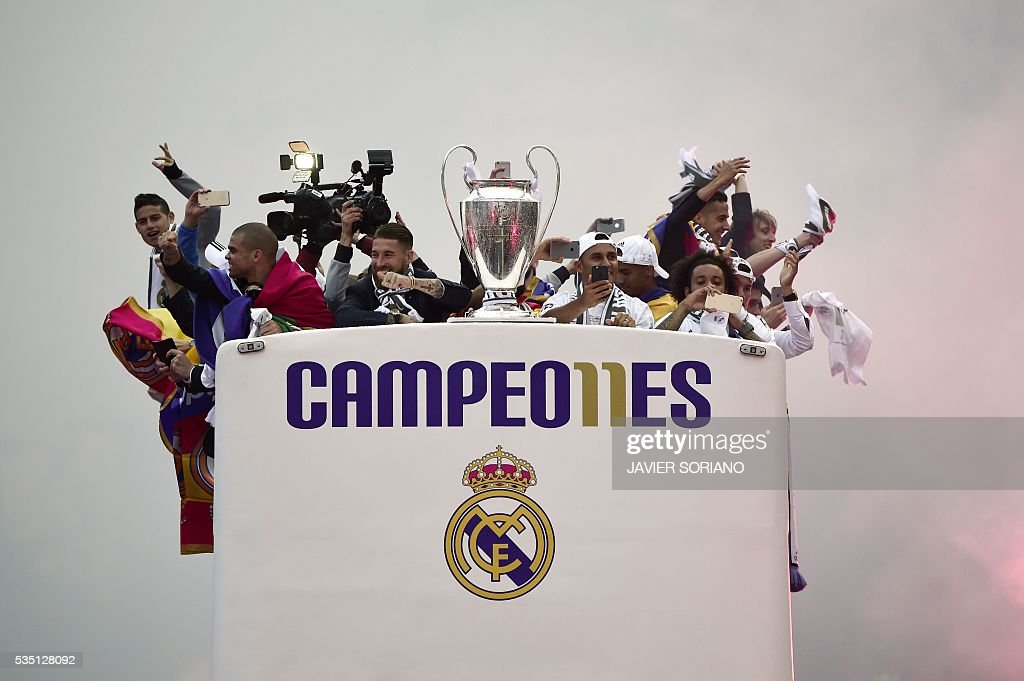 Real Madrid players hold up the trophy celebrating the team's win as they arrive by bus on Plaza Cibeles in Madrid on May 29, 2016 after the UEFA Champions League final foobtall match between Real Madrid CF, Club Atletico de Madrid held in Milan, Italy. / AFP / JAVIER