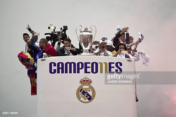 TOPSHOT Real Madrid players hold up the trophy celebrating the team's win as they arrive by bus on Plaza Cibeles in Madrid on May 29 2016 after the...
