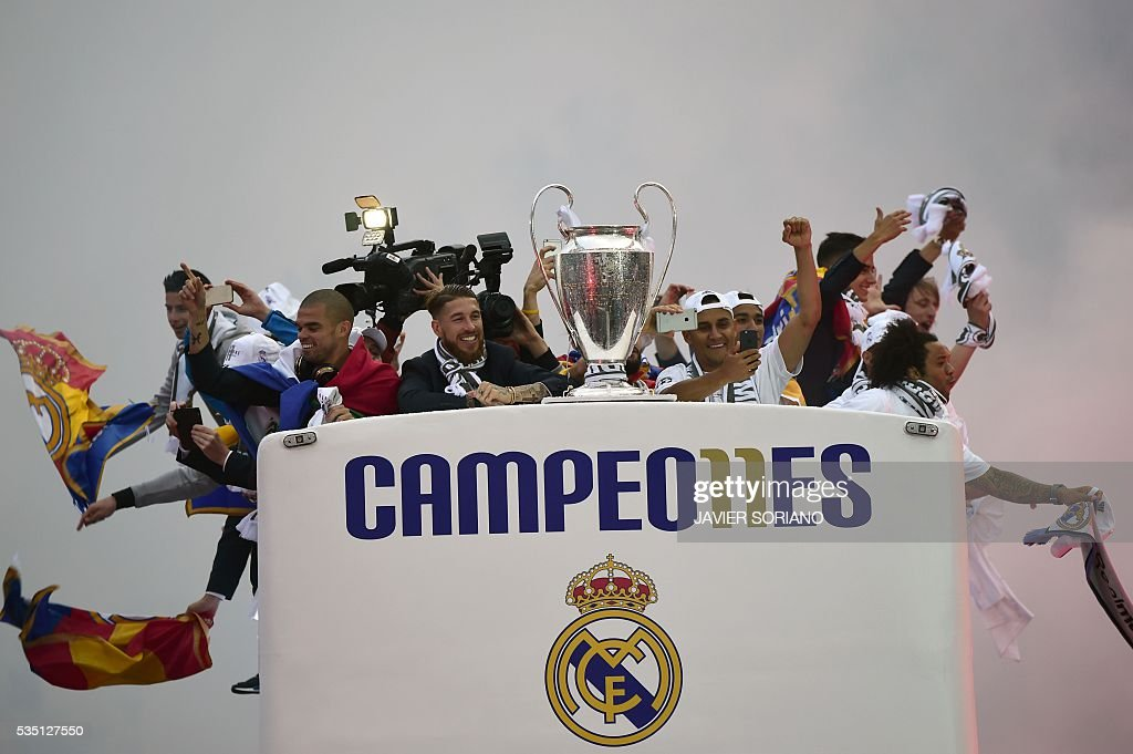 Real Madrid players hold up the trophy from the bus as they celebrate the team's win arriving on Plaza Cibeles in Madrid on May 29, 2016 after the UEFA Champions League final foobtall match between Real Madrid CF, Club Atletico de Madrid held in Milan, Italy. / AFP / JAVIER