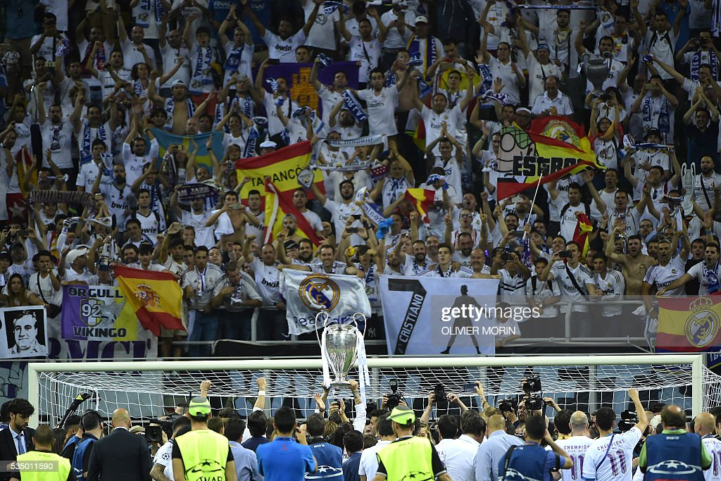 Real Madrid players lift the trophy as they celebrate with supporters winning the UEFA Champions League final football match over Atletico Madrid at San Siro Stadium in Milan, on May 28, 2016. / AFP / OLIVIER