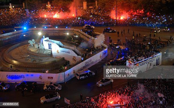 Real Madrid players on board the team bus celebrate their UEFA Champions League final win with fans at Cibeles Square in Madrid on May 24 2014 after...