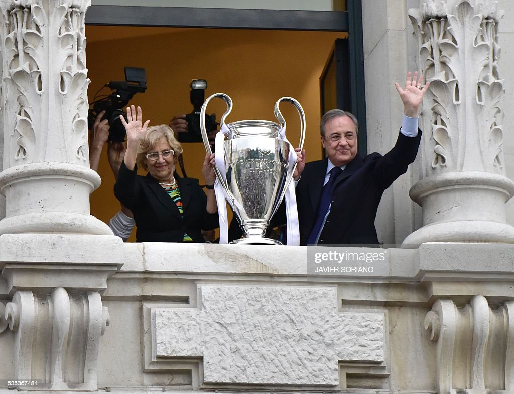 Real Madrid President Florentino Perez (R) and mayor of Madrid Manuela Carmena wave as they show the trophy from Madrid town hall's balcony on May 29, 2016 the day after winning the UEFA Champions League final foobtall match against Club Atletico de Madrid, held in Milan, Italy on May 28, 2016. / AFP / JAVIER