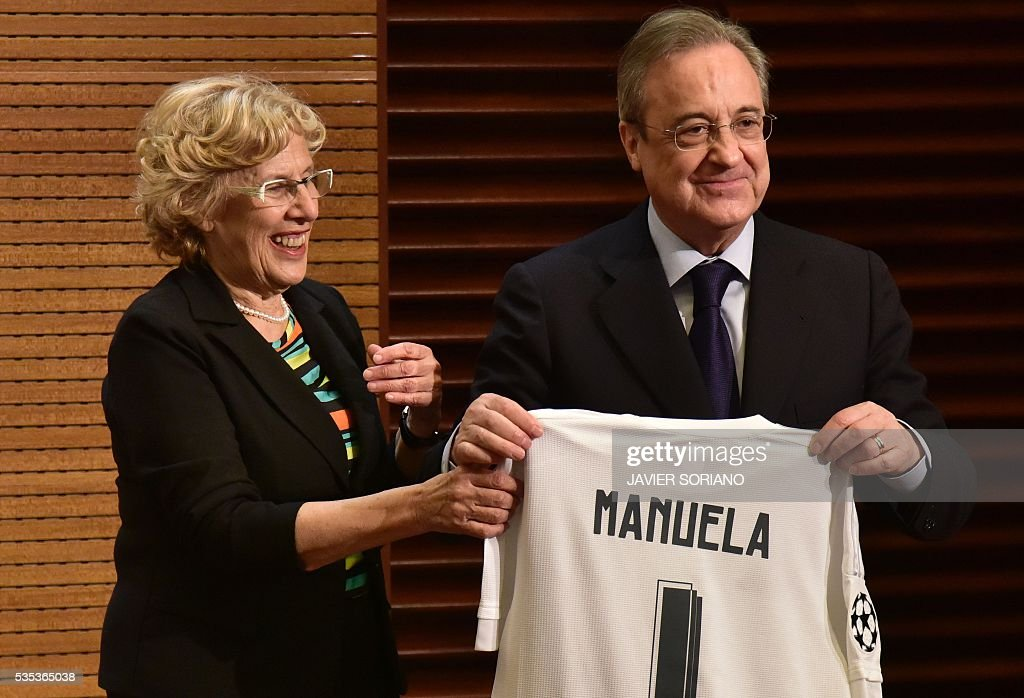 Real Madrid President Florentino Perez (R) gives a Real Madrid jersey to Mayor of Madrid Manuela Carmena in Madrid town hall on May 29, 2016 the day after winning the UEFA Champions League final foobtall match against Club Atletico de Madrid, held in Milan, Italy on May 28, 2016. / AFP / JAVIER