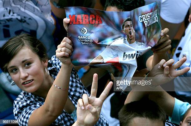 Real Madrid young supporters hold pictures of Real Madrid's new player Portuguese Cristiano Ronaldo before his official presentation at the Santiago...