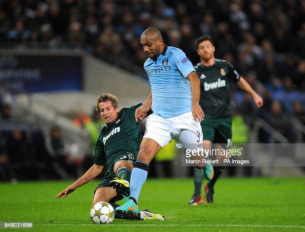 Real Madrid's Alexandre Fabio Coentrao and Manchester City's Sisenando Maicon battle for the ball