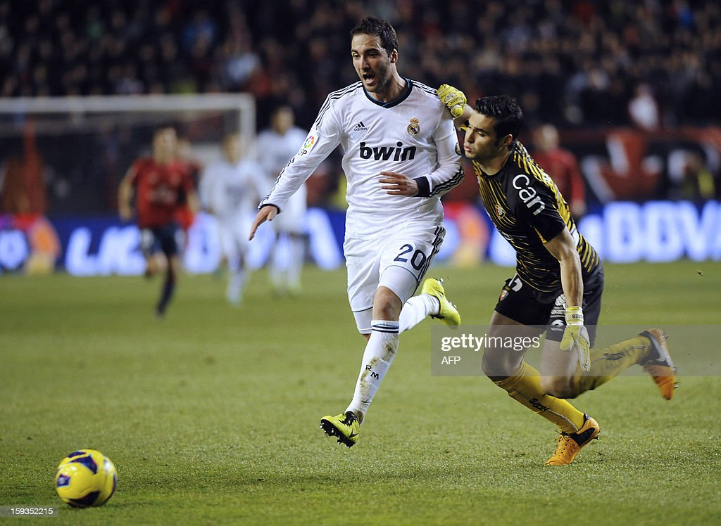 Real Madrid's Argentinian forward Gonzalo Higuain (L) vies with Osasuna's goalkeeper Andres (R) during the Spanish league football match CA Osasuna vs Real Madrid CF at the Reyno de Navarra stadium in Pamplona on January 12, 2013. AFP PHOTO / ANDER GILLENEA