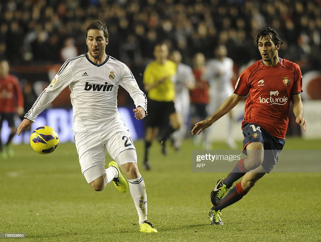 Real Madrid's Argentinian forward Gonzalo Higuain (L) vies with Osasuna's defender Alejandro Arribas (R) during the Spanish league football match CA Osasuna vs Real Madrid CF at the Reyno de Navarra stadium in Pamplona on January 12, 2013.