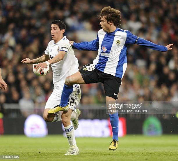 Real Madrid's Argentinian midfielder Angel di Maria vies with Hercules' defender Kiko Femenia during their Spanish league football match Real Madrid...