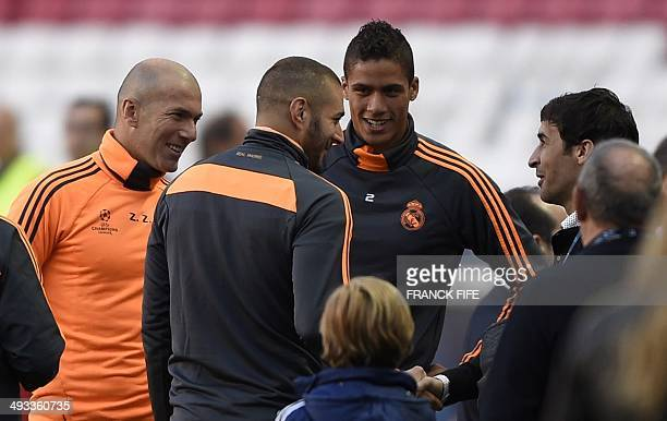 Real Madrid's assistant manager Zinedine Zidane speaks with former Real Madrid forward Raul Gonzalez with Real Madrid's French forward Karim Benzema...