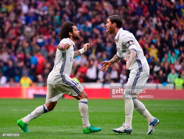 TOPSHOT Real Madrid's Brazilian defender Marcelo celebrates a goal with Real Madrid's defender Sergio Ramos during the Spanish league football match...