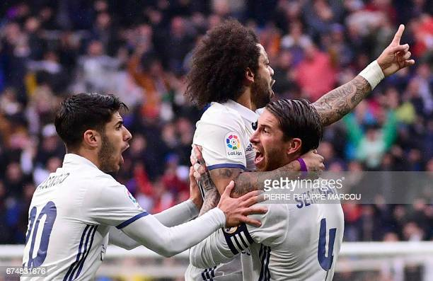 Real Madrid's Brazilian defender Marcelo celebrates after scoring with Real Madrid's midfielder Marco Asensio and Real Madrid's defender Sergio Ramos...
