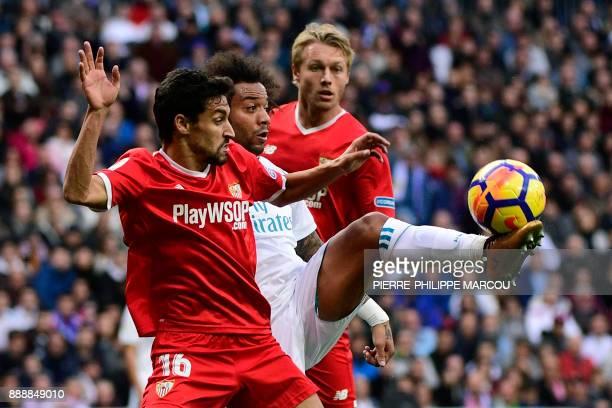 Real Madrid's Brazilian defender Marcelo challenges Sevilla's Spanish midfielder Jesus Navas and Sevilla's Danish defender Simon Kjaer during the...