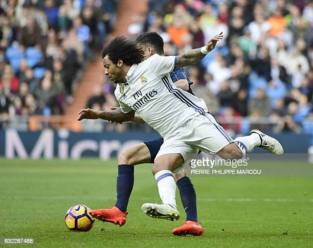 TOPSHOT Real Madrid's Brazilian defender Marcelo vies with Malaga's midfielder Juanpi during the Spanish league football match Real Madrid CF vs...