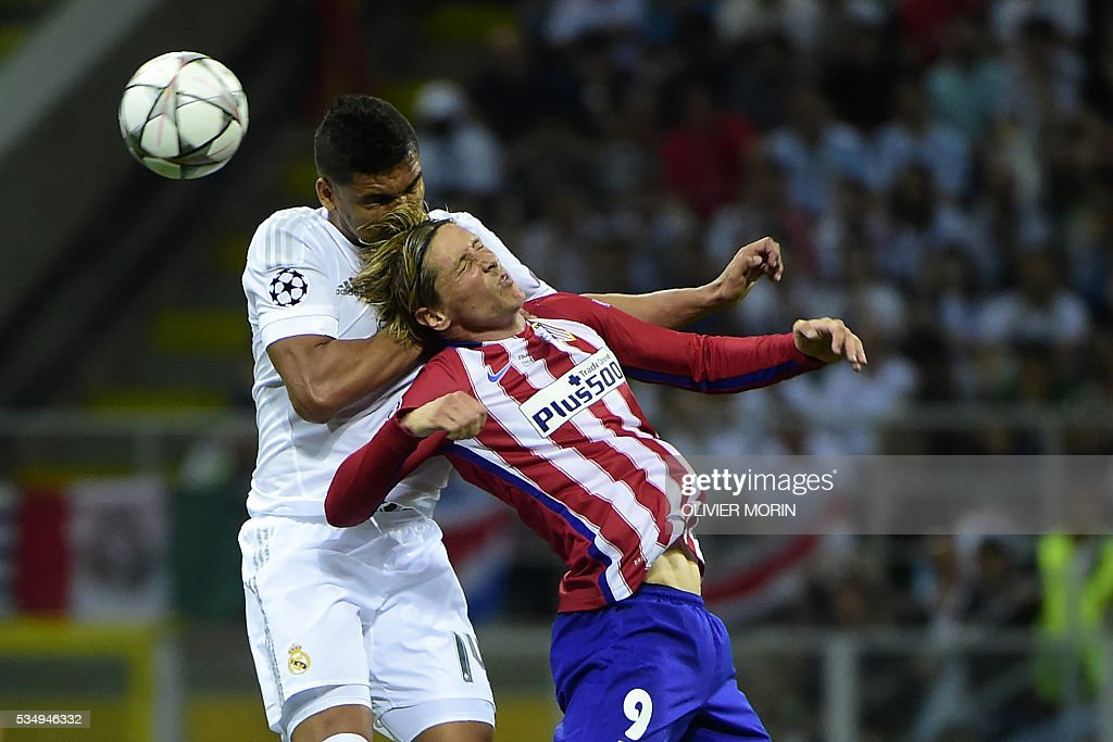 Real Madrid's Brazilian midfielder Casemiro (L) and Atletico Madrid's Spanish forward Fernando Torres jump for the ball during the UEFA Champions League final football match between Real Madrid and Atletico Madrid at San Siro Stadium in Milan, on May 28, 2016. / AFP / OLIVIER