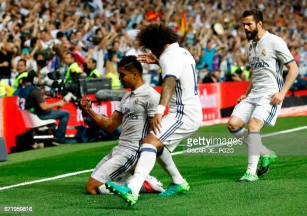 Real Madrid's Brazilian midfielder Casemiro celebrates a goal with teammates during the Spanish league football match Real Madrid CF vs FC Barcelona...