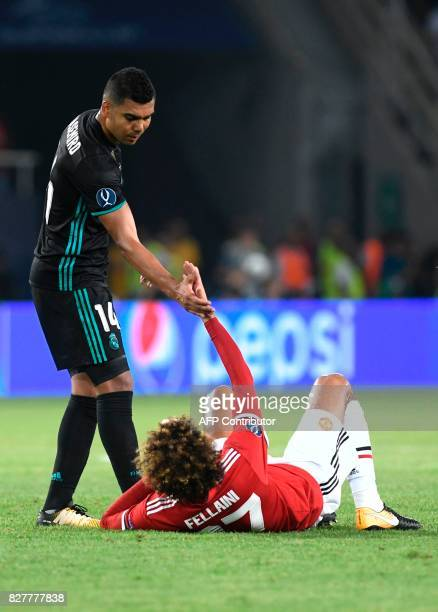 Real Madrid's Brazilian midfielder Casemiro helps Manchester United's Belgian midfielder Marouane Fellaini during the UEFA Super Cup football match...
