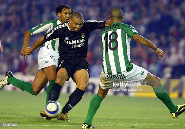 Real Madrid's Brazilian Ronaldo is about to score a goal against Betis between Betis player Benjamin and Tais during a Spanish soccer League match at...