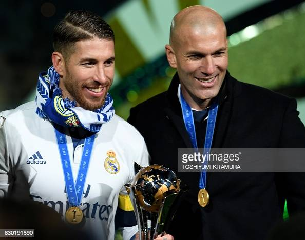 Real Madrid's captain and defender Sergio Ramos holding a championship trophy poses with head coach Zinedine Zidane after they won the Club World Cup...