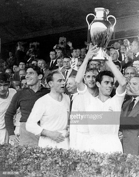 Real Madrid's captain Jose Santamaria with teammates Rogelio Dominguez and Alfredo Di Stefano standing next to him holds aloft the European Champions...