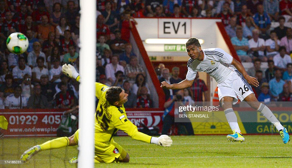 Real Madrid's Casemiro (R) scores a goal past Bournemouth's goalkeeper Darryl Flahaven (L) during the pre-season friendly football match between Bournemouth and Real Madrid at the Goldsands Stadium in Bournemouth, England on July 21, 2013.