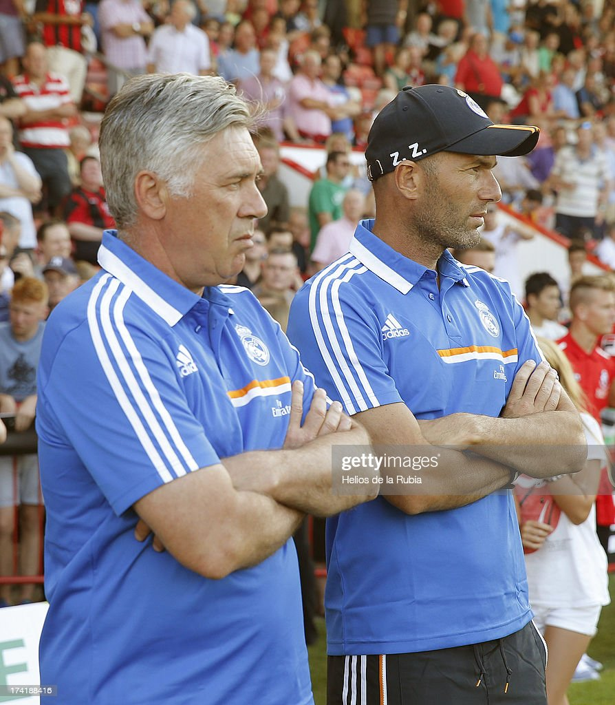 Real Madrid's coach <a gi-track='captionPersonalityLinkClicked' href=/galleries/search?phrase=Carlo+Ancelotti&family=editorial&specificpeople=226747 ng-click='$event.stopPropagation()'>Carlo Ancelotti</a> (L) and assistant <a gi-track='captionPersonalityLinkClicked' href=/galleries/search?phrase=Zinedine+Zidane&family=editorial&specificpeople=172012 ng-click='$event.stopPropagation()'>Zinedine Zidane</a> looks on as his team play during the pre-season friendly football match between Bournemouth and Real Madrid at the Goldsands Stadium in Bournemouth, England on July 21, 2013 at Goldsands Stadium on July 21, 2013 in Bournemouth, England.