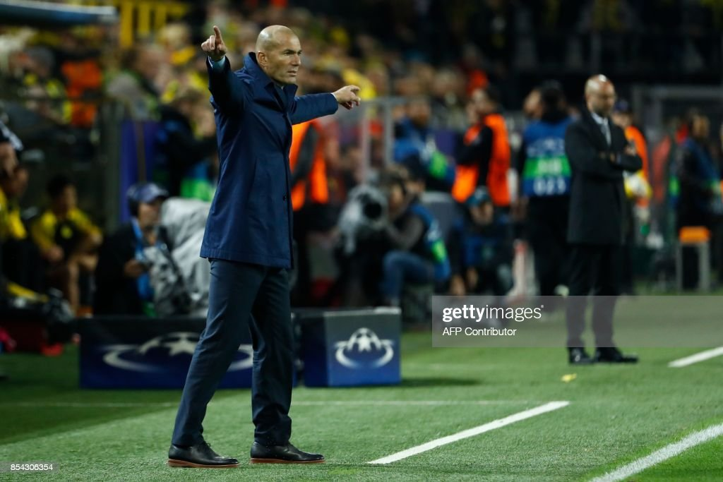 Real Madrid's coach from France Zinedine Zidane (L) react on the sidelines during the UEFA Champions League Group H football match BVB Borussia Dortmund v Real Madrid in Dortmund, western Germany on September 26, 2017. / AFP PHOTO / Odd ANDERSEN