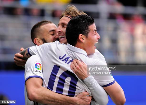 Real Madrid's Colombian midfielder James Rodriguez celebrates with teammates French forward Karim Benzema and Croatian midfielder Luka Modric after...